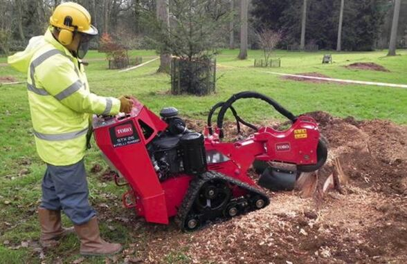 A man is standing behind a stump grinding machine and removing a stump. He's dressed in safety gear from head to toe. Has ear and eye protection as well. The background is green grass and a Forrest.